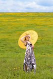 Standing girl with parasol, sky. Standing young girl with yellow parasol on meadow with sky behind, arm raised stock images