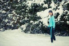 Standing girl wearing winter sportswear, trees background Royalty Free Stock Image