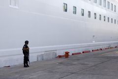 Standing Guard. An armed soldier watches over a boat on a dock in Mexico Royalty Free Stock Image