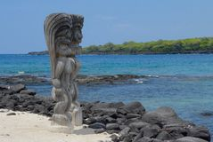 Standing Guard. Two ki`i, wooden images of Hawaiian gods, stand guard over the by at Pu`uhonua o Honaunau National Historic Park in Hawaii royalty free stock photos