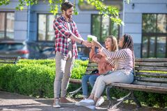 Free Standing Guy With Glasses Of Coffee And Two Girls On Bench Royalty Free Stock Photos - 190665448