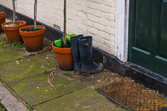 Standing high waders with beautiful brown pots at the entrance t. O the building, green door Stock Images