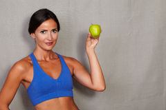 Standing lady showing apple in gym clothing Royalty Free Stock Photos
