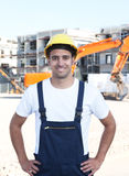 Standing latin construction worker with red excavator Stock Photo