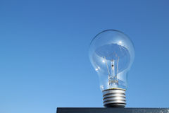 Standing light bulb close up in the blue sky Royalty Free Stock Photography