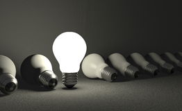 Standing light bulb in row of lying ones on gray Stock Photo