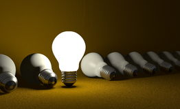 Standing light bulb in row of lying ones on yellow Royalty Free Stock Photography