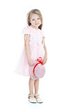Standing little blonde girl. In pink dress with hat in hands Royalty Free Stock Photo