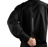 Standing man in black with knife for backs Royalty Free Stock Photos