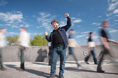 Standing man with the lifted hands. Among moving pedestrians royalty free stock image