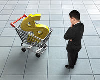 Standing man looking at shopping cart with golden dollar sign. High angle view Stock Photos
