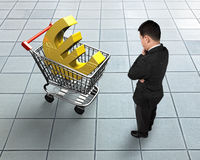 Standing man looking at shopping cart with golden euro sign. High angle view Royalty Free Stock Photos