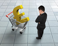 Standing man looking at shopping cart with golden pound sterling. Symbol, high angle view Stock Photography