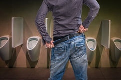 Standing man peeing to a urinal in restroom royalty free stock image