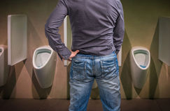 Standing man peeing to a urinal in restroom Stock Image