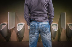 Standing man peeing to a urinal in restroom Royalty Free Stock Photo