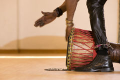 Standing man playing drum. Standing African man playing drum on floor, red cords, hands in movement Stock Images