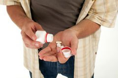 Standing man pouring out tablets on palm Stock Image