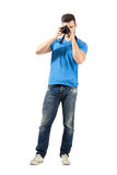 Standing man taking photo with dslr looking at camera Royalty Free Stock Photos