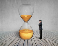Standing manager looking the hourglass Royalty Free Stock Images