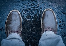 Standing in the middle of puddle during rainfall