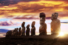 Standing moai in Easter Island at sunrise. Standing moai in Easter Island against rising sun and orange sky Stock Photo