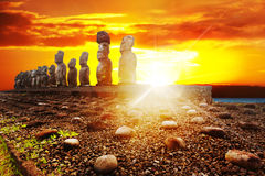Standing moais in Easter Island in dramatic orange sunset Royalty Free Stock Photo