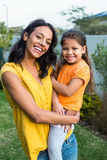 Standing mother holding her daughter outdoors Stock Photography