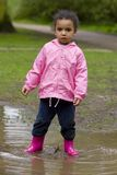Standing In a Muddy Puddle. A little mixed race girl in pink coat and boots standing in a muddy puddle Stock Image