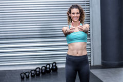 Standing muscular woman gesturing thumbs up Royalty Free Stock Photography
