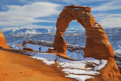 Standing Next to Delicate Arch. A man stand next to Delicate Arch during a winter afternoon in Arches National Park, Utah Royalty Free Stock Photos