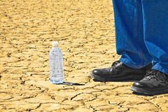Standing Next To Desert Bottled Water. A man is standing next to a bottle of water with it sitting on a desert playa Royalty Free Stock Images