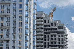 Standing next to the house in various stages of construction. Two adjacent high-rise residential buildings in various stages of construction Stock Image