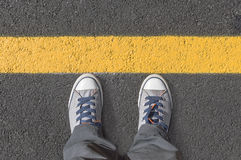 Standing next to yellow street lines. Royalty Free Stock Photo
