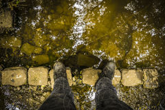 Standing on an old stones arranged as a bridge. Standing looking down an old bridge while exploring the river lea Royalty Free Stock Photos