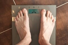 Free Standing On The Weight Scale. Overweight / Underweight. Royalty Free Stock Photos - 187062808