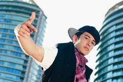 Standing One Arm Out. A hip hop dude standing in front of modern condos with pointing hand out Royalty Free Stock Image