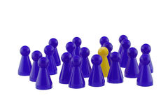 Standing out. Single yellow playing figure standing out in a blue crowd Stock Image