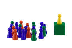 Standing out. Single yellow figure addressing a colorful crowd Royalty Free Stock Photo