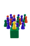 Standing out. Single yellow figure addressing a colorful crowd Royalty Free Stock Photography