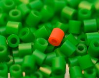 Standing out. Red plastic bead among many green beads Royalty Free Stock Image