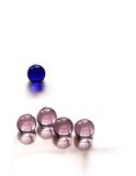 Standing out from the crowd #1. One blue marble ahead of 4 pink marbles. concepts: standing out from the crowd, leader, unique etc Royalty Free Stock Photo