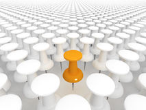 Standing out from the crowd. Orange thumbtack standing out from the white crowd of others Royalty Free Stock Photo