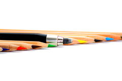 Standing out from the crowd. Some coloured crayons and the big one Stock Photography