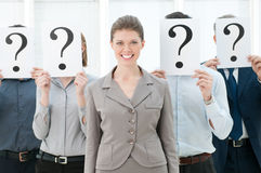 Standing out of the crowd. Happy smiling business women standing out of the crowd with other people hiding their faces behind a question mark sign Royalty Free Stock Images