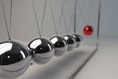 Standing out of a crowd. Chrome balancing spheres know as Newton's Cradle (pendulum Stock Photo