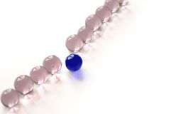 Standing out from the crowd #3. One blue marble moving ahead of a line of pink marbles on a white background with copy space Stock Photo