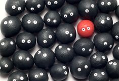 Standing out from the crowd. The idea of being different, distinguished among the others. Little plasticine balls with eyes. White background Stock Photo