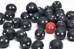 Standing out from the crowd. The idea of being different, distinguished among the others. Little plasticine balls with eyes. White background Royalty Free Stock Photography