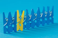 Standing out of the crowd concept with painted clothespins. Macro shot Royalty Free Stock Images